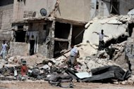 "Civilians search for personal belongings in the rubble of their house following shelling from Syrian government forces in the northern city of Aleppo on August 25. Syrian President Bashar al-Assad said on Sunday the foreign ""conspiracy"" against his country would be defeated, as his forces were accused of a bloody rampage"