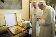 Pope Francis (L) exchanges a gift with Pope Emeritus Benedict XVI at the Castel Gandolfo summer residence, south of Rome March 23, 2013. REUTERS/Osservatore Romano