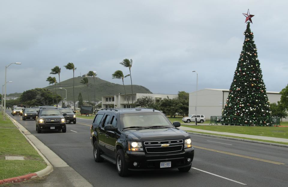President Barack Obama's motorcade makes its way past a Christmas tree on the Marine Base Hawaii in Kaneohe, Hawaii, Saturday, Dec. 24, 2011. President Obama played golf at the base in the afternoon during his holiday vacation. (AP Photo/Eric Risberg)