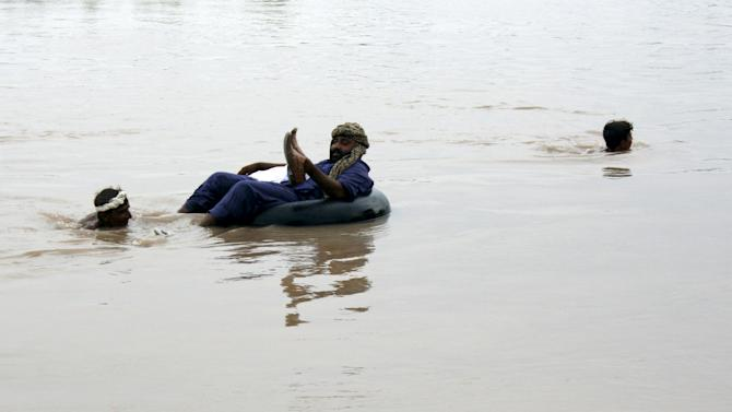 Local farm workers help a man cross the flooded Chenab river in Chinoit