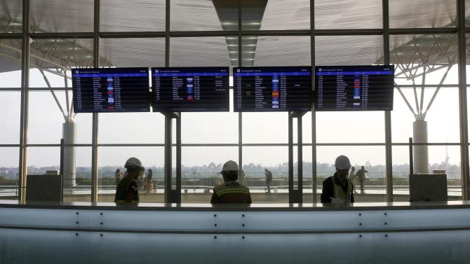 Workers stand underneath flight information screens at the new terminal two wing at Noi Bai international airport in Hanoi