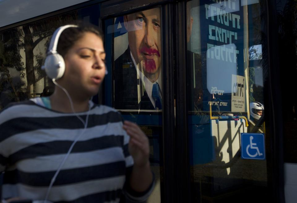 A woman jogs past a vandalized election campaign billboard of Israeli Prime Minister and Likud Party leader Benjamin Netanyahu that is reflected on a bus window in Tel Aviv, Israel, Monday, Jan. 21, 2013.  The general elections will be held on Tuesday, Jan. 22, 2013. (AP Photo/Ariel Schalit)