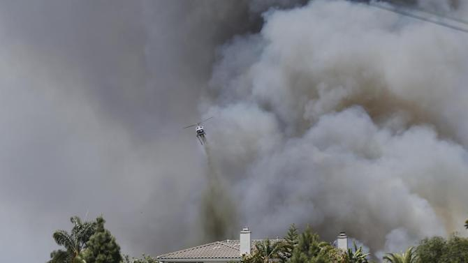 FILE - In this May 14, 2014 file photo, a helicopter drops fire fighting material over a house as smoke envelopes the area in Carlsbad, Calif. Fire-hardened Southern Californians know that when the Santa Ana winds blow, a wildfire probably isn't very far behind, the only questions are where and how bad it will be. A new mapping tool developed by the U.S. Forest Service will help homeowners and emergency responders get a better handle on both those questions with detailed color-coded early warning system that will indicate which areas have the highest risk of a devastating blaze during the hot, dry wind events.  (AP Photo, File)