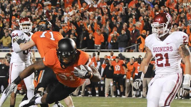 Oklahoma Stat's Parker Graham (71) blocks as Oklahoma's Dejuan Miller (24) and Tom Wort (21) watch Oklahoma State's Jeremy Smith (31) scores a touchdown during the first quarter of an NCAA college football game in Stillwater, Okla., Saturday, Dec. 3, 2011. (AP Photo/Brody Schmidt)