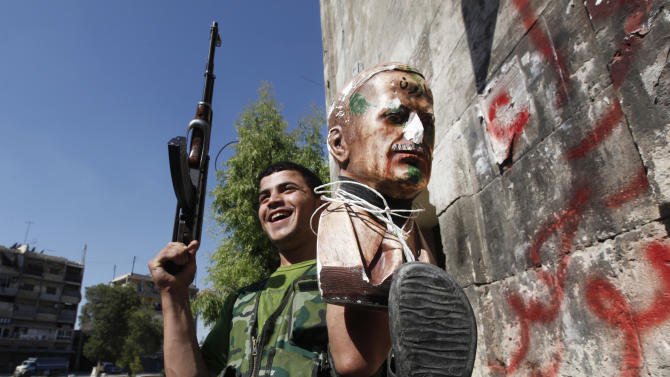 FILE - In this Monday, Sept. 24, 2012 file photo, a Free Syrian Army soldier, holds up statue for the late Syrian President Hafez Assad which is attached to a shoe, at the old city of Aleppo, Syria. With even his most powerful ally, Russia, losing faith in him, President Bashar Assad may appear to be heading for a last stand against rebel forces who have been waging a ferocious battle to overthrow him for nearly two years. But Assad still has thousands of elite and loyal troops behind him, and analysts say that even if he wanted to give up the fight, it's unclear those around him would let him abandon ship and leave them to an uncertain fate. (AP Photo/Hussein Malla, File)