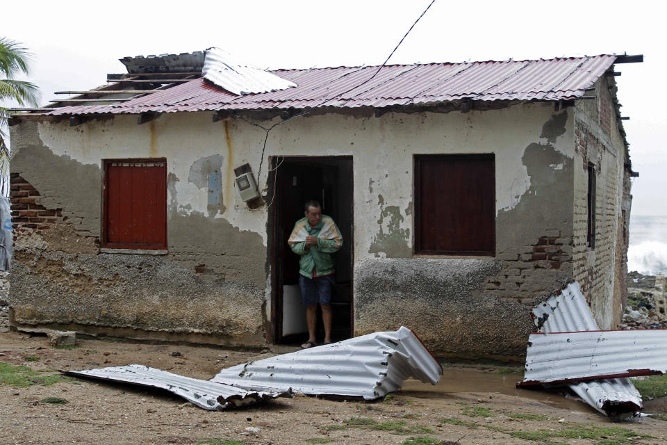 Nelson Carballosa stands in his home's doorway after the passing hurricane Sandy damaged his roof in Gibara, Cuba, Thursday, Oct. 25, 2012. Hurricane Sandy blasted across eastern Cuba on Thursday as a potent Category 2 storm and headed for the Bahamas after causing at least two deaths in the Caribbean. (AP Photo/Franklin Reyes)