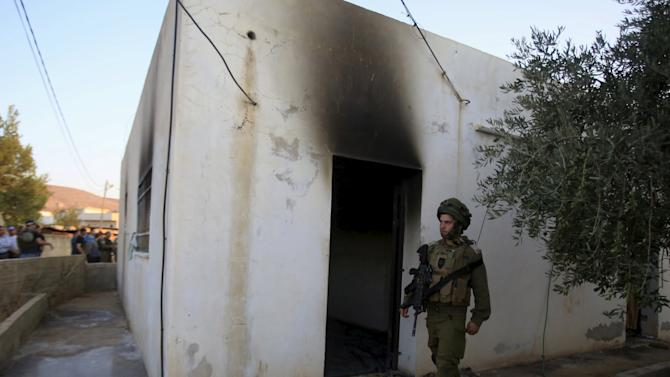 An Israeli soldier walks past a house that had been torched in a suspected attack by Jewish extremists killing an 18-month-old Palestinian child, injuring a four-year-old brother and both their parents at Kafr Duma village near Nablus