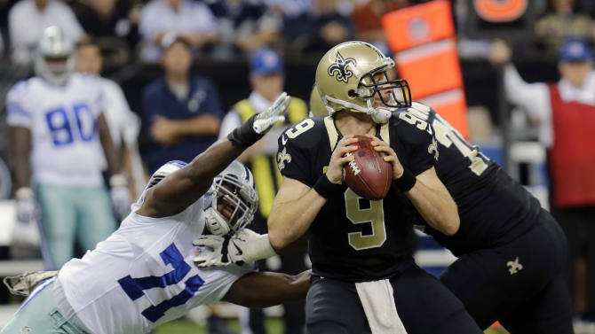 New Orleans Saints quarterback Drew Brees (9) passes under pressure from Dallas Cowboys defensive end Everette Brown (71) in the first half of an NFL football game in New Orleans, Sunday, Nov. 10, 2013. (AP Photo/Bill Haber)