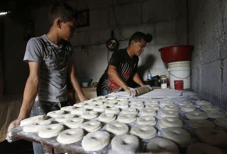 Victor Toruno makes doughnuts with Francisco Jimenez at Toruno's home, which also serves as a bakery, in the Hialeah neighborhood in Managua