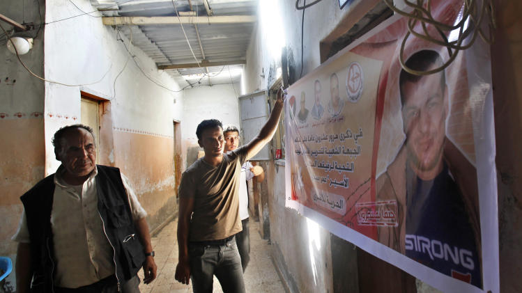 "In this Friday, July 26, 2013, photo, Issa Masoud, 75, left, helps his sons put up a banner of his jailed son at Shati Refugee Camp in Gaza City. His son Omar, 40, was arrested in May 1993 for killing an Israeli lawyer. Israel's Cabinet is to decide Sunday whether to release dozens of long-term Palestinian prisoners as part of U.S. Secretary of State John Kerry's attempt to restart Israeli-Palestinian talks after five years of diplomatic paralysis. The Arabic on the banner reads, ""On the 20th anniversary of his arrest, PFLP (the Popular Front for the Liberation of Palestine) salute comrade prisoner Omar Masoud, Freedom for prisoners."" (AP Photo/Adel Hana)"