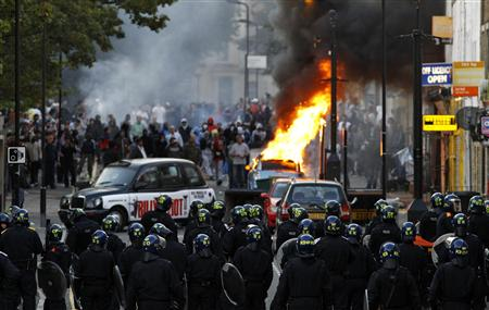 REUTERS/Luke MacGregor - Police officers in riot gear block a road near a burning car on a London street.