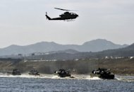 South Korean K1A1 tanks cross a river as an AH-1S helicopter flies overhead during a military drill in Wonju, east of Seoul, on February 8, 2012. Over the past five years, Asia and Oceania accounted for 44 percent in volume of conventional arms imports, the Stockholm International Peace Research Institute said