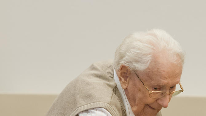 Defendant Oskar Groening arrives on the dock of the court in Lueneburg, northern Germany, Tuesday, April 21, 2015. The  93-year-old former Auschwitz guard faces trial on 300,000 counts of accessory to murder, in a case that will test the argument that anyone who served at a Nazi death camp was complicit in what happened there. (Julian Stratenschulte/Pool Photo via AP)