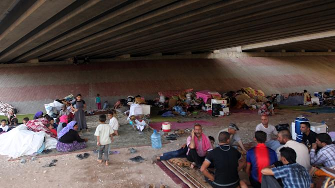 Displaced Iraqis from the Yazidi community gather under a bridge where they found refuge after Islamic State militants attacked the town of Sinjar on August 17, 2014 on the outskirts of Dohuk
