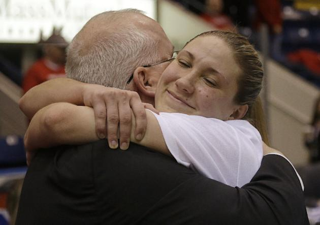 Marist guard Casey Dulin, right, hugs her head coach Brian Giorgis before the trophy presentation ceremony after winning an NCAA woman's MAAC conference championship basketball game against Quinni