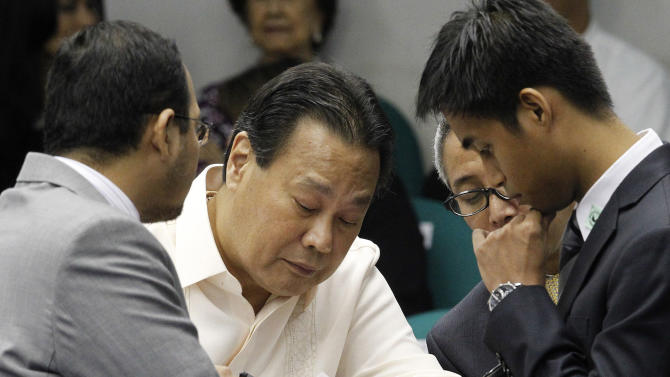"""Supreme Court Chief Justice Renato Corona, with a hep-lock attached to his hand, signs a waiver authorizing bank institutions to open his dollar and peso bank accounts during his impeachment trial at the Senate in Manila Friday, May 25, 2012. Corona on Tuesday read a lengthy testimony and """"wished to be excused"""" without being cross-examined by the prosecution. (AP Photo/Romeo Ranoco, Pool)"""