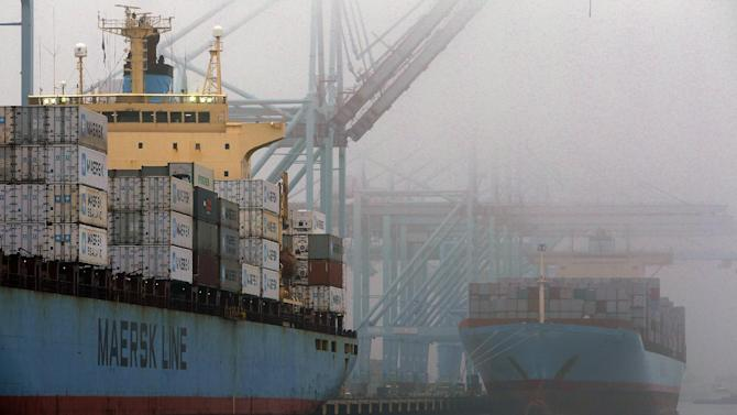 In this Wed. Dec. 5, 2012, photo, containers are unloaded from cargo ships at  the Port of Los Angeles.  The U.S. economy unexpectedly shrank from October through December, the first quarterly drop since 2009 and a reminder of the economy's vulnerability as automatic cuts in government spending loom. (AP Photo/Nick Ut)