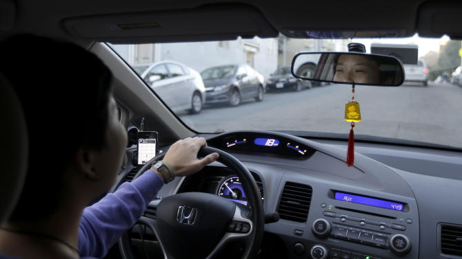 In this Jan. 4, 2013 photo,  Lyft driver Nancy Tcheou drives in San Francisco, Friday. Fed up with traditional taxis, city dwellers are tapping their smartphones to hitch rides from strangers using mobile apps that allow riders and drivers to find each other. Internet-enabled ridesharing services such as Lyft, Uber and Sidecar are expanding rapidly in San Francisco, New York and other U.S. cities, billing themselves as a high-tech, low-cost alternative to cabs. (AP Photo/Jeff Chiu)