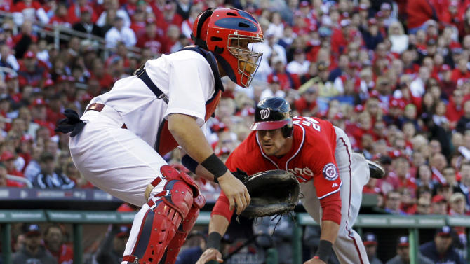 Washington Nationals' Ian Desmond, right, scores on a single by Jordan Zimmermann as St. Louis Cardinals catcher Yadier Molina, left, looks for the throw during the second inning in Game 2 of baseball's National League division series, Monday, Oct. 8, 2012, in St. Louis. (AP Photo/Jeff Roberson)
