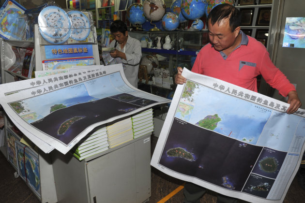In this Sept. 19, 2012 photo, a costumer picks copies of newly-published maps of disputed islands, called Diaoyu in China and Senkaku in Japan, at a state-owned book store in Beijing, China. China hastily published the map to help maintain public outrage over the Japanese government's purchase of some of the islands from their private Japanese owners. Beijing also has engaged in another type of mapmaking that may end up escalating the conflict. (AP Photo) CHINA OUT