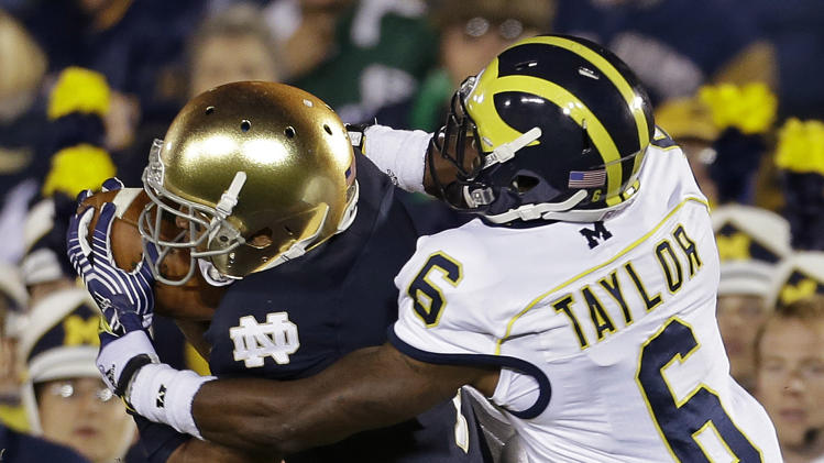 Notre Dame's TJ Jones makes a catch against Michigan's Raymon Taylor during the first half of an NCAA college football game Saturday, Sept. 22, 2012, in South Bend, Ind. (AP Photo/Darron Cummings)