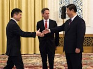 Gary Locke (left) shakes hand with Chinese Vice President Xi Jinping (right) as US Treasury Secretary Timothy Geithner looks on at the Great Hall of the People in Beijing in January. Locke said Beijing's exchange rate policy makes the yuan currency artificially cheap
