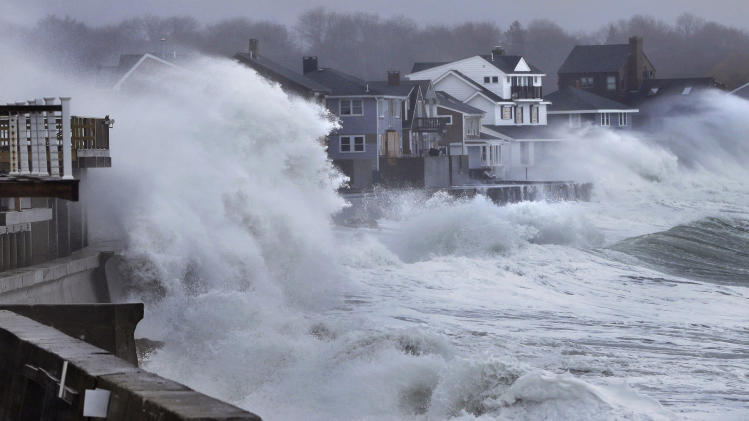 Ocean waves crash over a seawall and into houses along the coast in Scituate, Mass., Thursday, March 7, 2013. A nor'easter is bringing wind-whipped, wet snow to Massachusetts, and coastal flooding is expected in communities still recovering from February's blizzard. (AP Photo/Steven Senne)