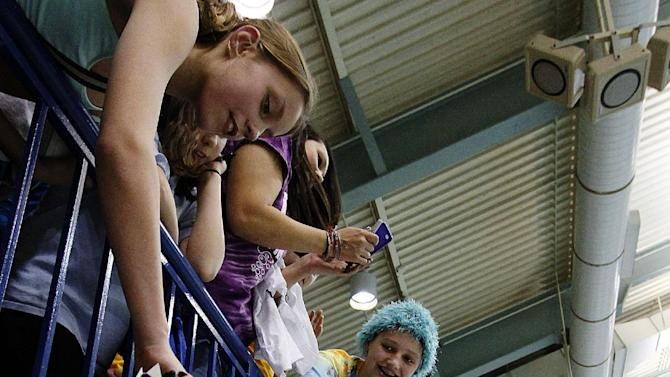 Missy Franklin signs autographs after competing at the USA Grand Prix swimming event, Sunday, Nov. 11, 2012, in Minneapolis. (AP Photo/Andy Clayton King)