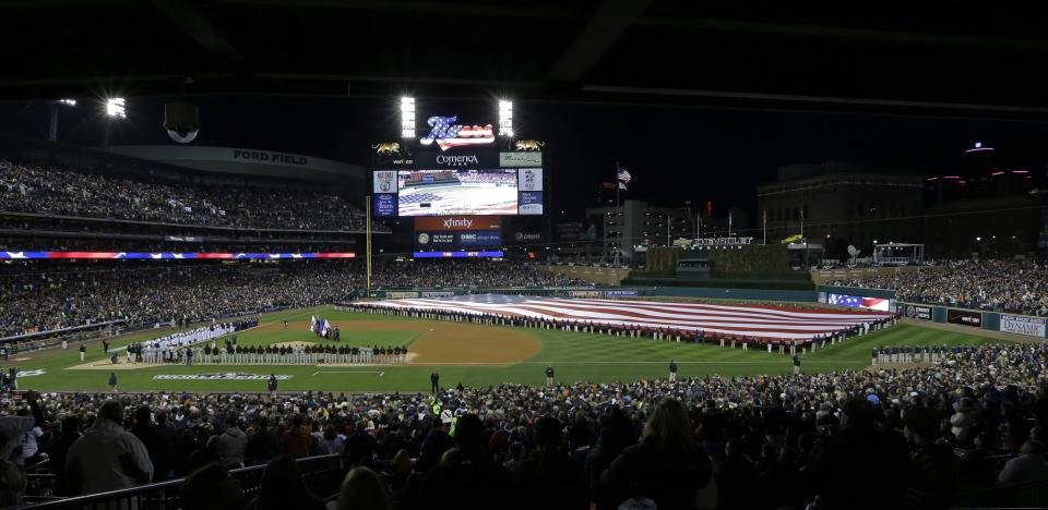 The San Francisco Giants and Detroit Tigers line up for the national anthem before Game 3 of baseball's World Series Saturday, Oct. 27, 2012, in Detroit. (AP Photo/Paul Sancya )