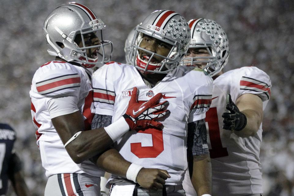 Ohio State quarterback Braxton Miller (5) celebrates his touchdown with teammates Michael Thomas, left, and Corey Linsley, right rear, during the third quarter of an NCAA college football game against Penn State in State College, Pa., Saturday, Oct. 27, 2012. (AP Photo/Gene J. Puskar)
