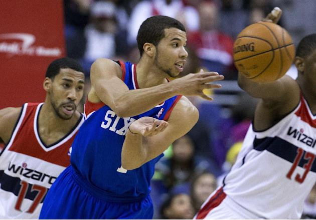Washington Wizards shooting guard Garrett Temple, left, looks on as Philadelphia 76ers point guard Michael Carter-Williams delivers a pass during the second half of an NBA basketball game on Monday, J