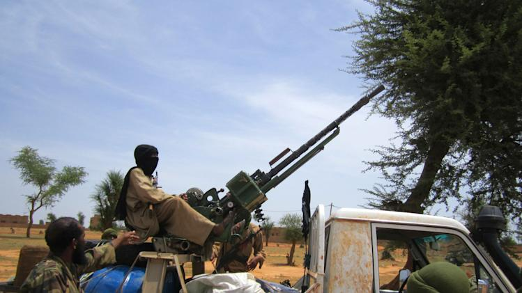 In this Thursday, Sept. 27, 2012 photo, Islamist commanders instruct 13-year-old fighter Abdullahi to man a pickup-mounted machine gun, during a meeting with an AP journalist, in Douentza, Mali.  Islamists in northern Mali have recruited and paid for as many as 1,000 children from rural towns and villages devastated by poverty and hunger. The Associated Press spoke with four children and conducted several dozen interviews with residents and human rights officials. The interviews provide evidence that a new generation in what was long a moderate and stable Muslim nation is becoming radicalized, as the Islamists gather forces to fight a potential military intervention backed by the United Nations. (AP Photo/Baba Ahmed)