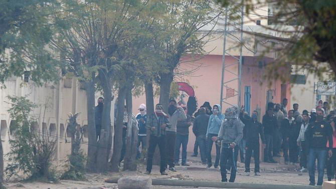 """Tunisian protesters clash with riot police, in Siliana, Tunisia, Saturday, Dec. 1, 2012. The army moved into a southwestern Tunisian town, an official and witnesses said Friday, the fourth day of protests that have injured more than 300 people. President Moncef Marzouki said on television that the North African country's government has not """"met the expectations of the people"""" and asked that a new one, smaller and specialized to deal with the unrest, be formed. The current government has about 80 members. (AP Photo/Amine Landoulsi)"""