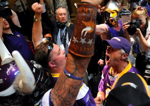 Minnesota Vikings fans, including Larry Spooner, right, in baseball cap, and David Gunderson, upper right, with face paint, celebrate after the Minnesota Senate voted to approve a new Vikings football stadium,Thursday afternoon, May 10, 2012 at the State Capitol in St. Paul, Minn. The Vikings are on the brink of getting a new stadium after the state Senate approved a plan that relies heavily on public financing. Gov. Mark Dayton has said he'll sign the measure, which makes Thursday's Senate approval the final hurdle for the nearly $1 billion stadium. The House passed it overnight. (AP Photo/The St. Paul Pioneer Press, Chris Polydoroff) MINNEAPOLIS STAR TRIBUNE OUT, MAGS OUT Chris Polydoroff)