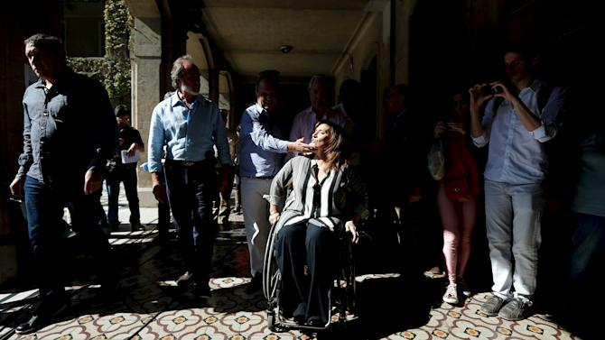 Lombardi, vice-mayor candidate, touches the face of mayor candidate Michetti of the PRO party, as they arrive to a polling station in Buenos Aires