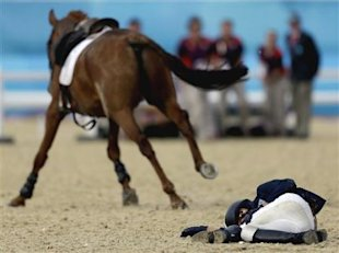 Woojin Hwang, of Korea, lays on the ground after getting bucked off his horse Shearwater Oscar, in the equestrian show jumping stage of the men&amp;#39;s mode