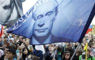 Supporters of Prime Minister and President-elect Vladimir Putin wave flags during a supporters rally in central Moscow