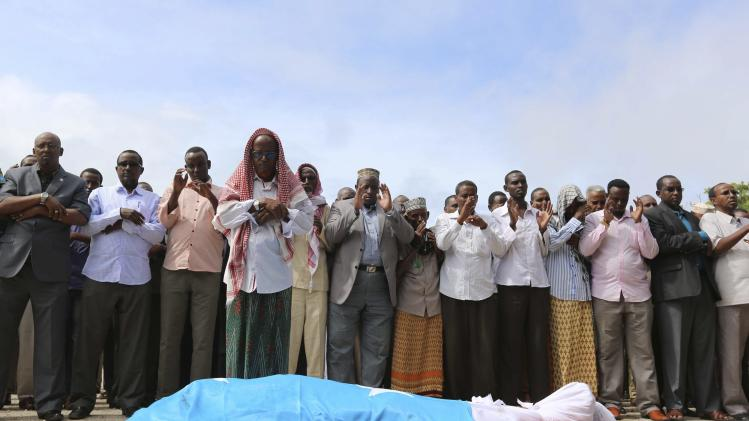 Members of the parliament and relatives pray near the body of Madeer in Mogadishu
