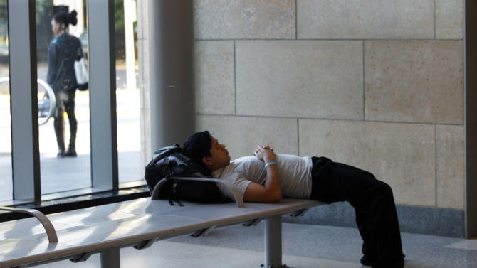 A man rests at the Trenton train station early Monday, Aug. 29, 2011, in Trenton, N.J., after some commuters were caught off guard when there was no train service. New Jersey Transit rail service was suspended Monday due to damage from Hurricane Irene. (AP Photo/Mel Evans)