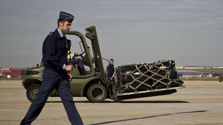 Some of the 17 tons of silver and gold coins scooped up from a Spanish warship, Nuestra Senora de las Mercedes, that sank during a 1804 gunbattle are escorted from a military plane to a warehouse after the planes carrying the treasure landed at the Torrejon De Ardoz military airbase, near Madrid, on Saturday Feb. 25, 2012. Two Spanish military C-130 transport planes landed out from Tampa's MacDill Air Force Base with the 594,000 coins and other artifacts retrieved after a five-year legal wrangle with Odyssey Marine Exploration company who had found the shipwreck off the Portuguese coast and flew the treasure back to the U.S. via Gibraltar in May 2007.(AP Photo/Daniel Ochoa de Olza)