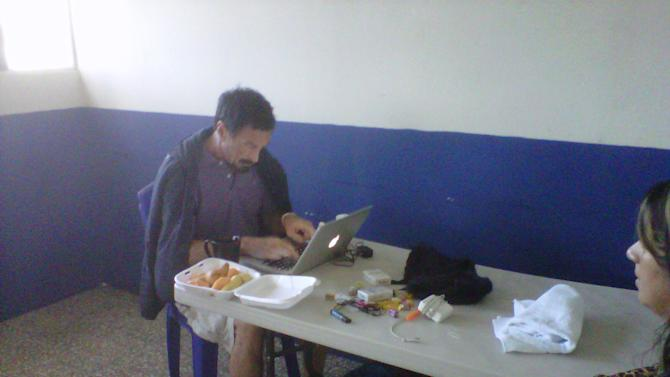 In this image made using a cell phone, software company founder John McAfee updates his blog at an immigration detention center in Guatemala City, Thursday, Dec. 6, 2012. The anti-virus guru was arrested at a hotel in an upscale neighborhood with the help of Interpol agents, hours after he said he would seek asylum in the Central American country. Guatemalan authorities were awaiting orders from their Foreign Ministry about whether to send him back to Belize, where he is a person of interest in the killing of a fellow expatriate American. Pictured at right is one of his lawyers, Karla Paz.(AP Photo/Sonia Perez)