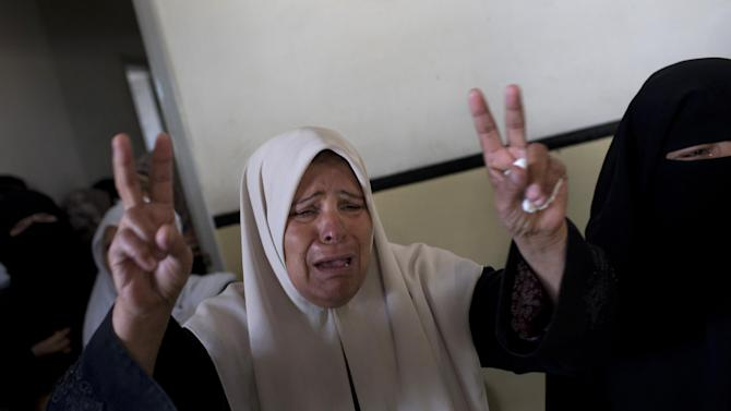 A relative of Hamas member Joudeh Shamallah makes the victory sign while weeping during Shamallah's funeral in Gaza City, Saturday, Nov. 24, 2012. According to family members, Shamallah was badly injured during the latest Israeli-Hamas fight and died from wounds Saturday. (AP Photo/Bernat Armangue)