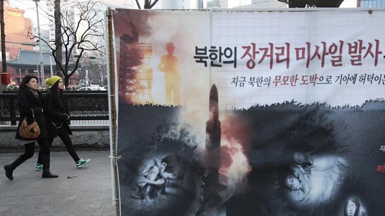 "A banner showing starving North Korean children and a rocket is displayed on a street in Seoul, South Korea, Thursday, Jan. 24, 2013. North Korea's top military body warned Thursday that the regime is poised to conduct a nuclear test in response to U.N. punishment, and made clear that its long-range rockets are designed to carry not only satellites but also warheads aimed at striking the United States. The writing reads "" Fired North Korean rocket for whom?"" (AP Photo/Ahn Young-joon)"