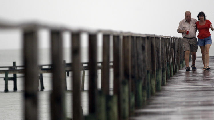 Donny and Mary Jones walk down a pier in the rain as Tropical Storm Don approaches the Texas Gulf Coast Friday, July 29, 2011, in Port Mansfield, Texas. (AP Photo/David J. Phillip)