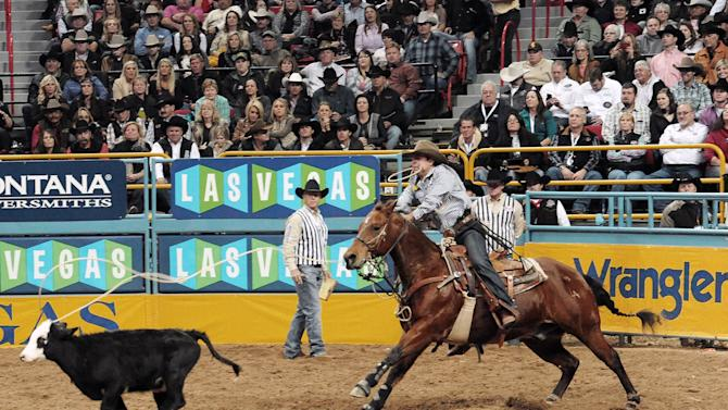 FILE - In this Dec. 12, 2013 file photo provided by the Las Vegas News Bureau, Randall Carlisle, of Baton Rouge, La., competes in the Tie-Down Event on Day 8 of the National Finals Rodeo at the Thomas & Mack Arena in Las Vegas. The National Finals Rodeo is planning to leave Las Vegas for Florida after 29 years, depriving Sin City of an event that brings nearly $100 million in economic impact annually as thousands of cowboys and rodeo fans descend on the city each December. (AP Photo/Las Vegas News Bureau, Glenn Pinkerton,File)