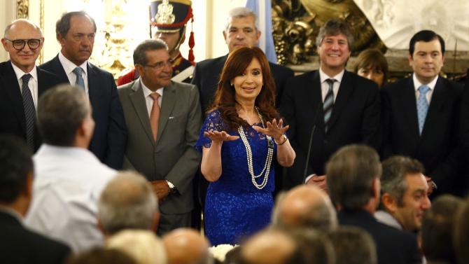 Argentina's President Cristina Fernandez de Kirchner stands in front of Vice President Amado Boudou during a ceremony in Buenos Aires