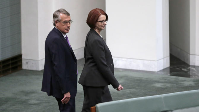 Former Australian Prime Minister Julia Gillard, right, with her former deputy Wayne Swan, arrive in chambers at parliament for question time for what is likely to be its last day before elections, in Canberra, Australia, Thursday, June 27, 2013. Gillard was dumped in a party ballot and Kevin Rudd was sworn in as Australian prime minister three years and three days after he was ousted from the same job in an internal government showdown. (AP Photo/Rick Rycroft)