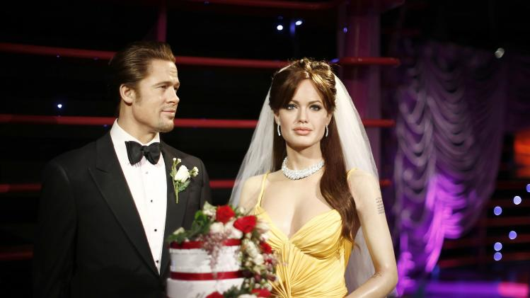 Wax models of actors Brad Pitt and Angelina Jolie are pictured with a wedding cake and bridal veil in celebration of their recent wedding, at the Madame Tussauds attraction in Sydney
