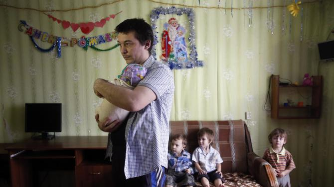 Anatoly Gorlov, husband of Russian activist Svetlana Davydova, spends time with their children at their home in Vyazma