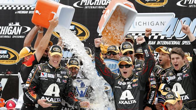 Jeff Gordon celebrates his victory with crew members after the NASCAR Sprint Cup Series Pure Michigan 400 auto race at Michigan International Speedway in Brooklyn, Mich., Sunday, Aug. 17, 2014